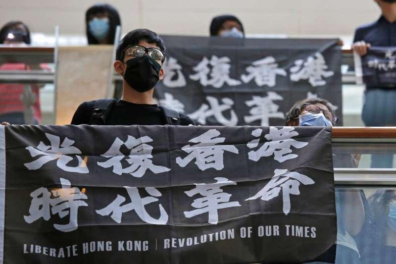 香港民眾高舉「光復香港、時代革命」的抗議布條。(美聯社)