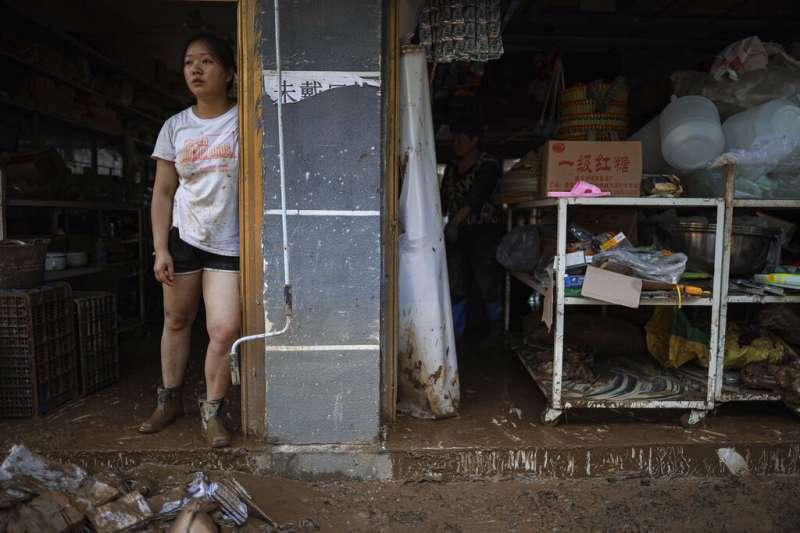 2020年6月13日,貴州省遵義市的洪水剛剛退去,一位居民望著殘破的家園發愣。(美聯社)