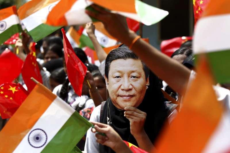 憤怒的印度民眾拿著習近平照片與印度國旗,高聲抗議中國軍隊進犯邊境。(美聯社)