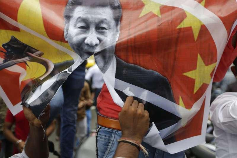 憤怒的印度民眾拿著習近平照片高聲抗議中國軍隊進犯邊境。(美聯社)