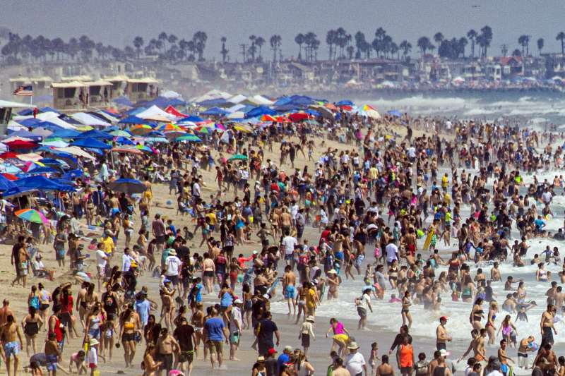 美國逐步啟動解封計劃,被新冠疫情憋壞了的人潮立刻塞滿景點。圖為加州杭亭頓海灘。(AP)