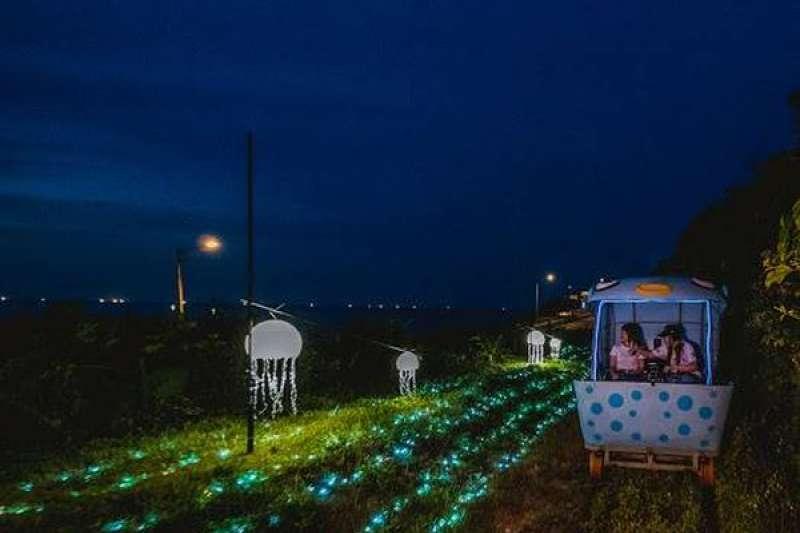 搭乘可愛俏皮的河豚車在海風與星光下出發,欣賞山野草叢間靜懿神祕的螢火蟲燈及象徵海洋浪花的燈海,充滿奇幻感的彩色泡泡與螢光水母漂浮其中,好玩又好拍。(圖/新北觀旅局提供)