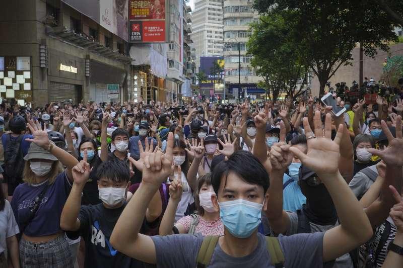 2020年7月1日,港人在《國安法》陰影下走上街頭,高舉代表「五大訴求、缺一不可」的手勢(AP)