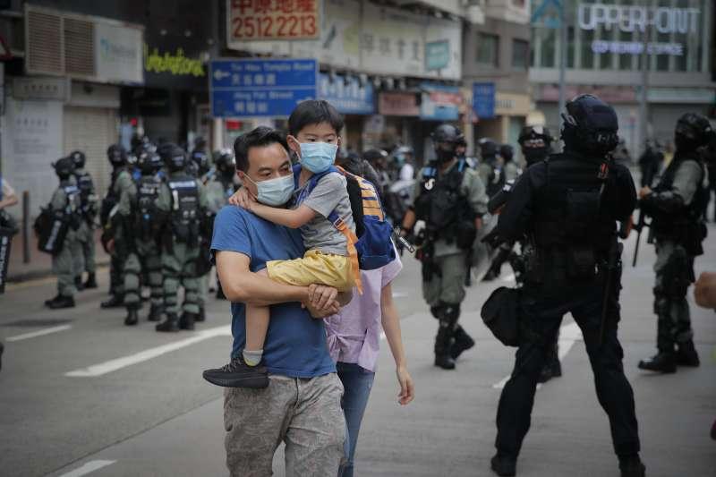 2020年7月1日,《國安法》陰影籠罩香港,一對父子走過嚴陣以待的防暴警察。(AP)