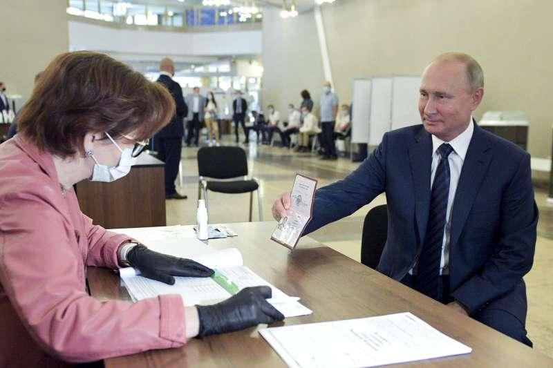 7月1日,俄羅斯總統普京(右)在投票前向選務人員出示證件(美聯社)