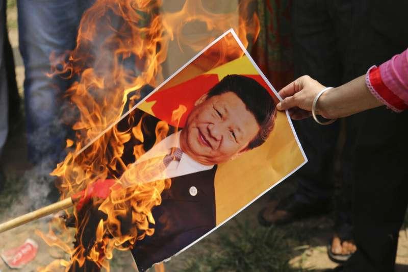中印邊界衝突讓兩國情勢急遽緊張,印度各地也紛紛舉行反中示威,習近平的照片也成了抗議道具。(美聯社)