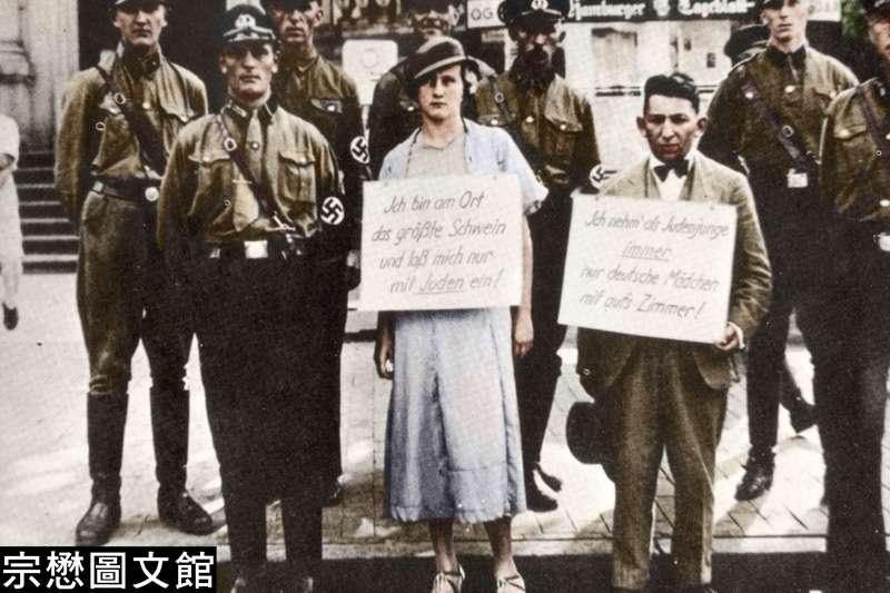 納粹衝鋒隊將一名猶太商人以及他的德國女性朋友壓到大街上當眾羞辱,男性猶太商人掛著字牌寫著「猶太人是豬」,女性友人頸上掛的字牌則寫著「我和猶太人交往」。(圖/徐宗懋圖文館)