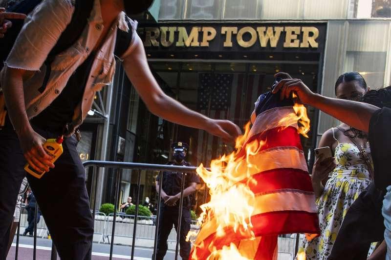 2020年7月4日美國國慶日,示威者在紐約川普大樓(Trump Tower)前焚燒美國國旗。(AP)