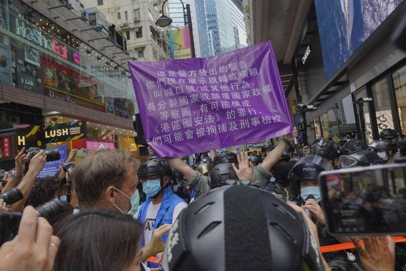 港警舉著「紫旗」警告民眾違反《港區國安法》,反遭民眾嘲笑。(美聯社)