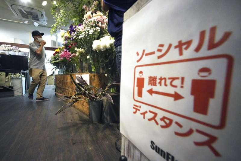 東京一間花店用宣導海報提醒客人「保持社交距離」。據美聯社報導,這波新冠疫情對日本經濟造成嚴重衝擊。(美聯社)