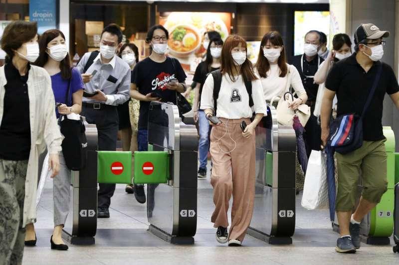 7月14日,橫濱車站裡戴著口罩的乘客們。(美聯社)