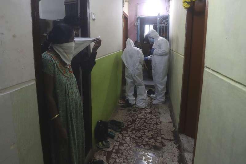 衛生防疫人員協助公寓消毒。新冠疫情期間,印度中低階層居住環境擁擠,難以落實社交隔離。(AP)