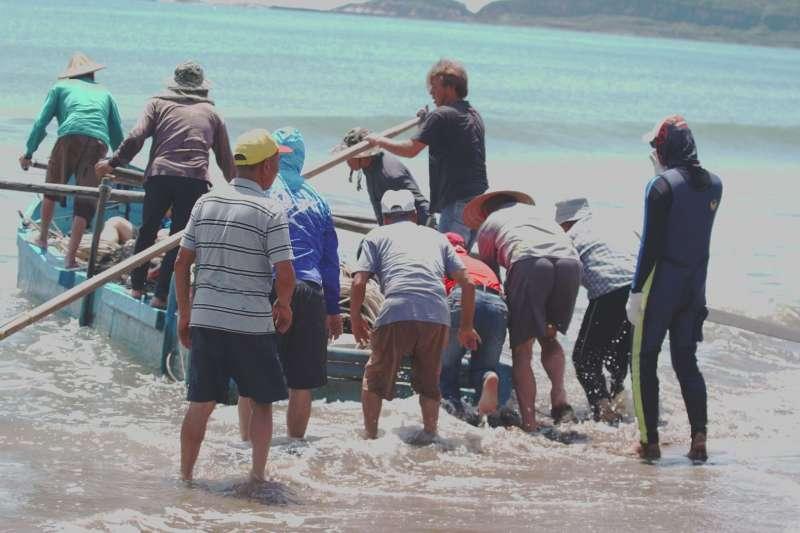 另項古老傳統捕魚方式為牽罟文化,划著舢舨的漁民,先將曳地網撒到海裡,再由岸上的人協力拖行魚網上岸。(圖/新北市文化局)