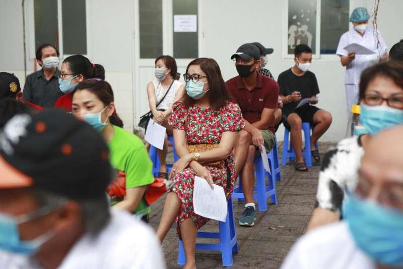 越南新一波新冠肺炎疫情爆發,民眾戴回口罩,排隊等待接受病毒篩檢。(AP)