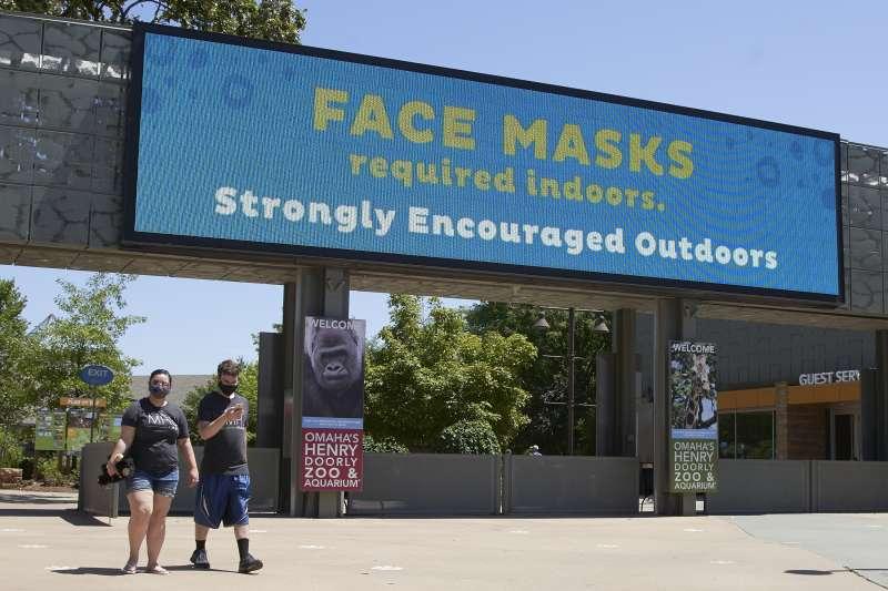 武漢肺炎疫情重創美國,許多學校網上開學,有兩組矽谷家庭原本只是暑假返台探親,後來決定至少長住台灣半年。(圖為美國內布拉斯加州歐馬哈動物園大門的戴口罩告示/AP)