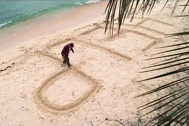 電影浩劫重生中,飾演Chuck的湯姆漢克斯在空難後在海灘上寫字求救。(圖/imdb)