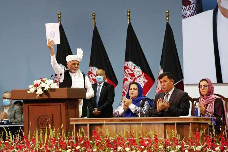 阿富汗部族大會決定同意釋放最後400名神學士成員,掃除直接和談唯一障礙,圖為阿富汗總統賈尼高舉大會決議文(AP)