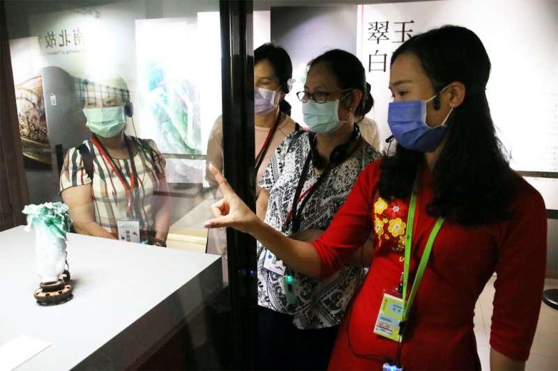 越南新住民范氏月(右1)指出翠玉白菜只有18公分高,但卻雕工精細,令人陶醉。(圖/內政部移民署提供)