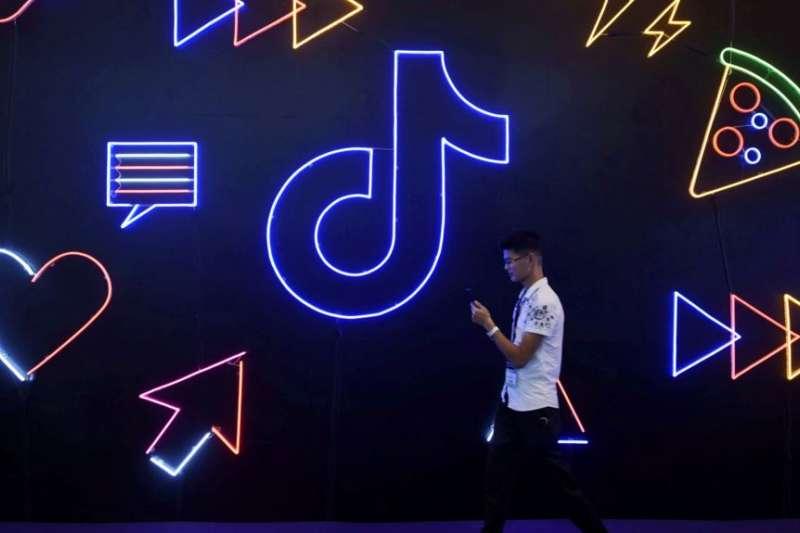 2019年10月18日行人走過杭州國際人工智能產品博覽會上的TikTok應用程式標誌。(美國之音)