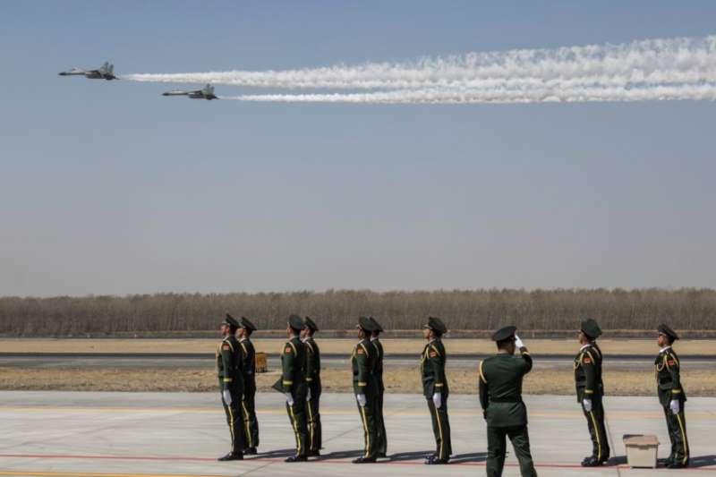 中國空軍兩架殲-11戰機在遼寧瀋陽一個機場低空飛行飛過一隊中國士兵。(2019年4月3日)(圖/美國之音)