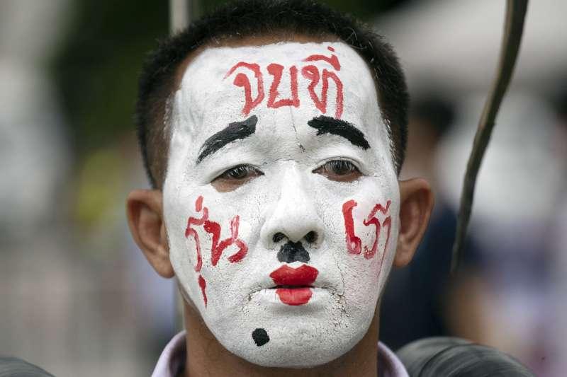 泰國近日爆發抗議學潮,要求總理下台並檢討君主制,一名示威者臉上寫著「終結在我們這世代」的字樣。(AP)