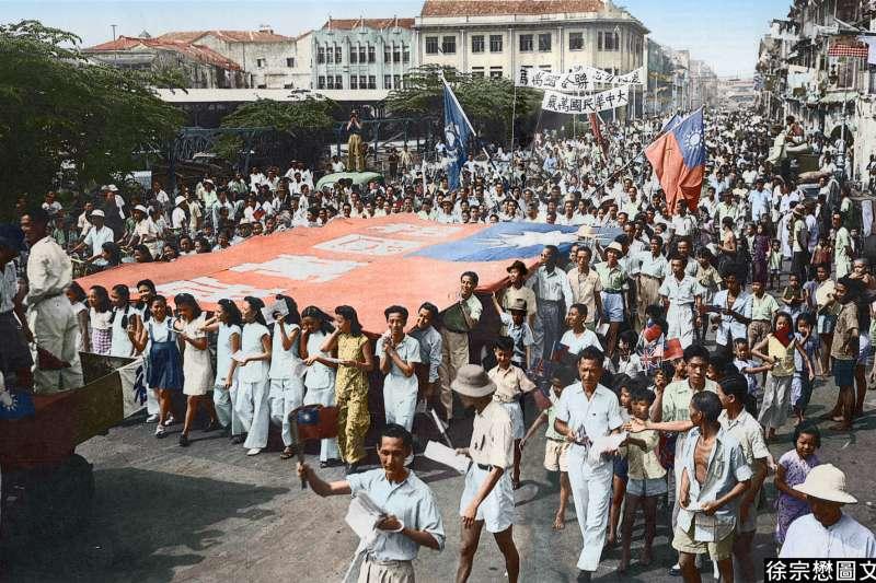 1945年9月12日,新加坡慶祝二戰勝利大遊行,華人青年男女高舉著一幅大型的中華民國國旗,上面有四個大字「祖國萬歲」。(圖/徐宗懋圖文館)