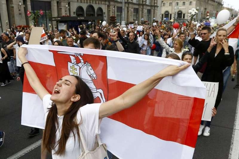 8月14日,白俄羅斯首都明斯克,一名女性示威者帶著歷史上具有獨立自由意義的旗幟上街抗議(美聯社)