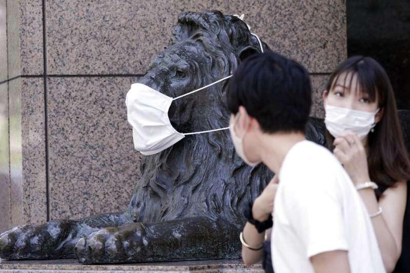 新冠疫情持續肆虐,有日本民眾也為商業大樓外的銅獅戴上口罩。(美聯社)