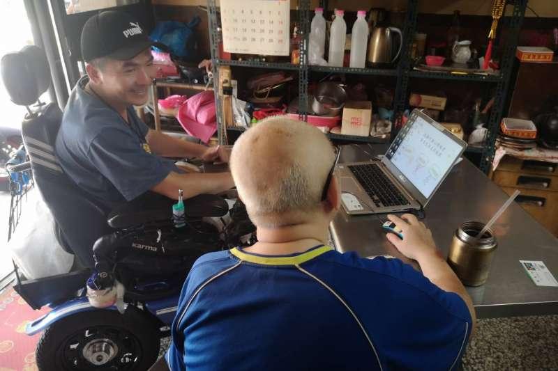 脊椎損傷身障者陳先生(左)發揮人溺己溺的大愛精神,坐輪椅到府教其他身障朋友電腦繪圖。(圖/高市社會局提供)