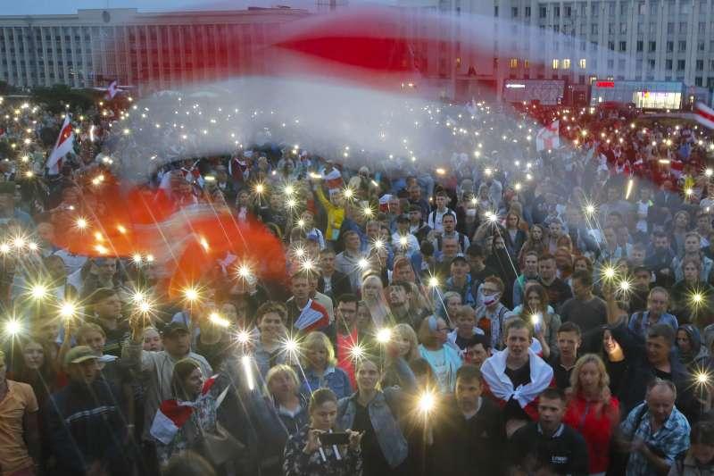 白羅斯反政府示威,抗爭者在集會時揮舞手機燈光與國旗。(AP)
