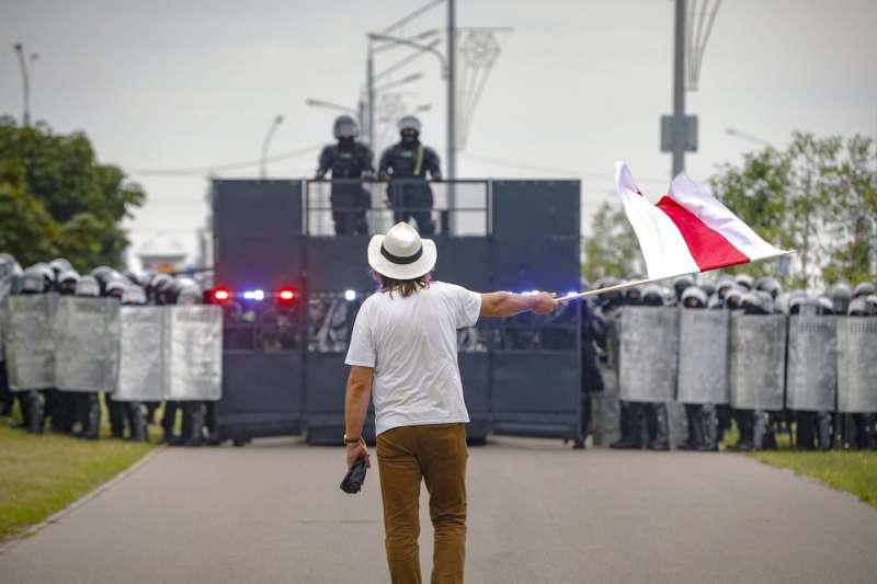 8月23日,一名白羅斯示威民眾與抗暴警察對峙(美聯社)