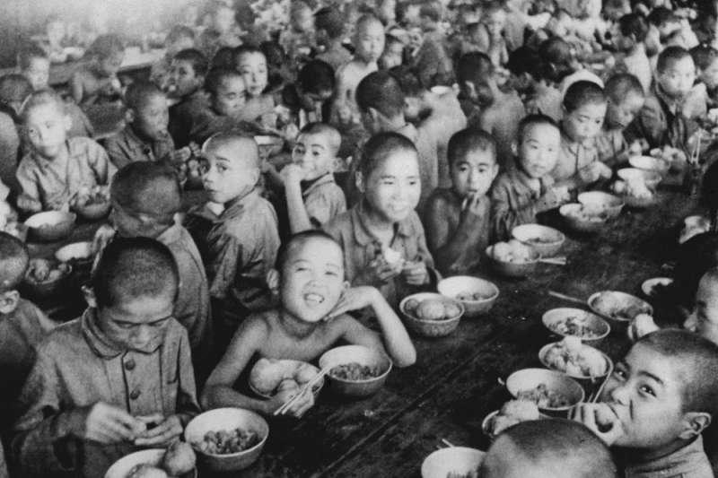 1946年,日本東京孤兒院內,孤兒們一起用餐(美聯社)