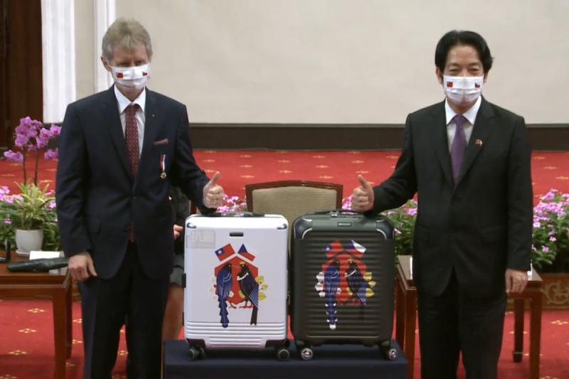 捷克參議院議長韋特齊(左)訪台,副總統賴清德(右)贈出代表「台捷友好」的行李箱,外觀由文總設計,箱體則是使用來自台南的「台灣之光」萬國通路(eminent)8月才剛上市的新款式。(取自總統府直播)
