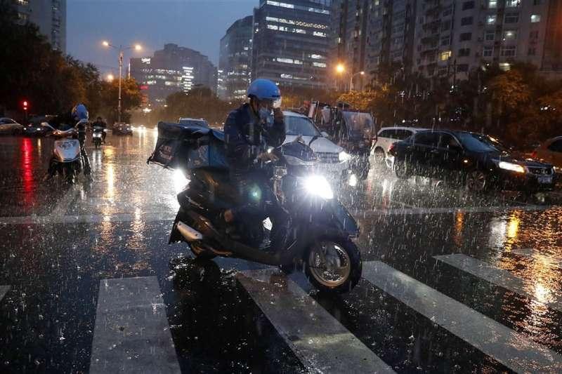 在外送點餐平台配送系統不斷優化下,中國外送員配送同樣公里數的時間越來越短,也面臨更多交通事故風險。圖為一名中國大陸外送員在大雨中爭分奪秒送餐,免得被扣錢。(中新社)