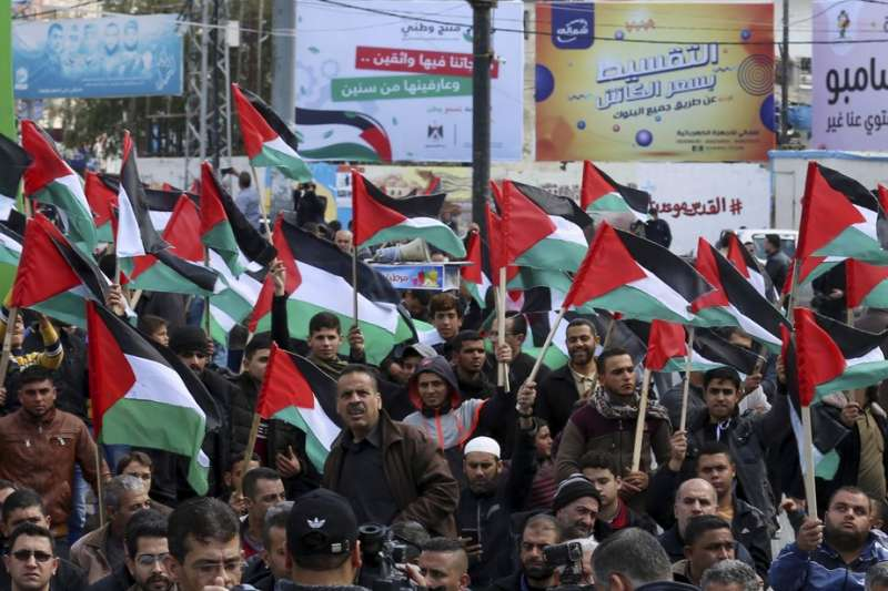 2020年2月21日,加薩地區的巴勒斯坦人揮舞國旗,抗議美國總統川普提出的中東和平方案。(AP)