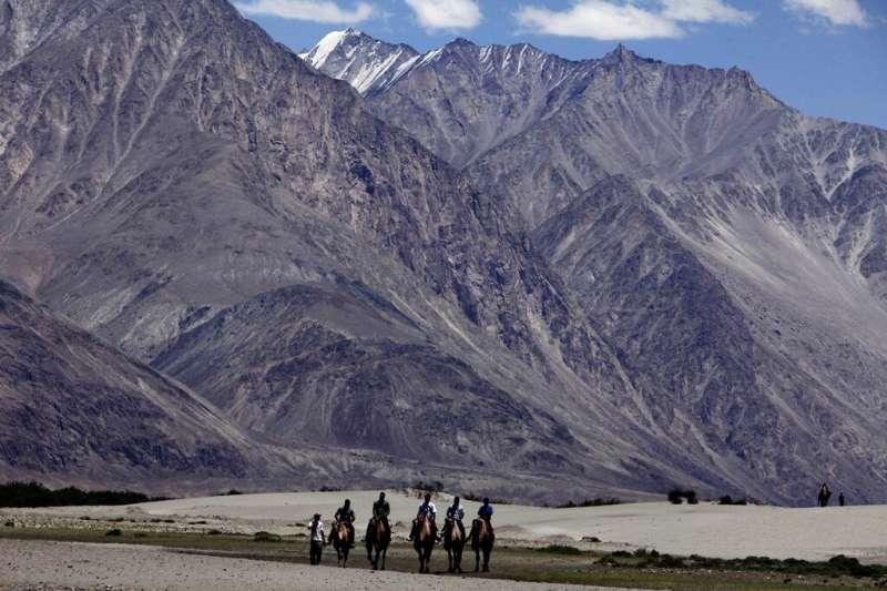 在這張資料照片中,數名遊客騎著雙峰駱駝在拉達卡地區遊覽。這個海拔數千公尺的中印邊界地帶,如今卻成為兩國對峙的最前線。(美聯社)