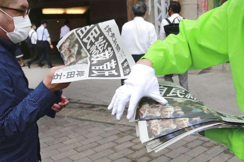 日本自由民主黨14日舉行總裁改選,菅義偉一如預期以高票勝出,日本讀賣新聞立刻在街頭發送快報。(美聯社)