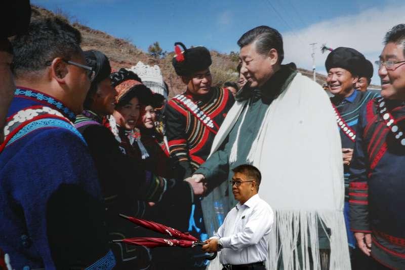 一名路人身後的大幅照片,顯示中國國家主席習近平在四川成都與少數民族會面。(美聯社)