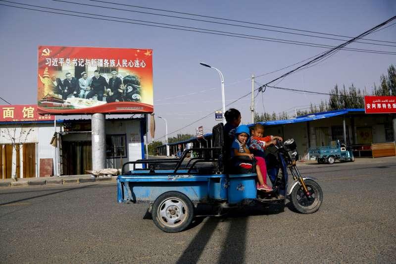 新疆和田市一名維吾爾族婦人與她的孩子,後方正好是習近平的宣傳看板。(美聯社)