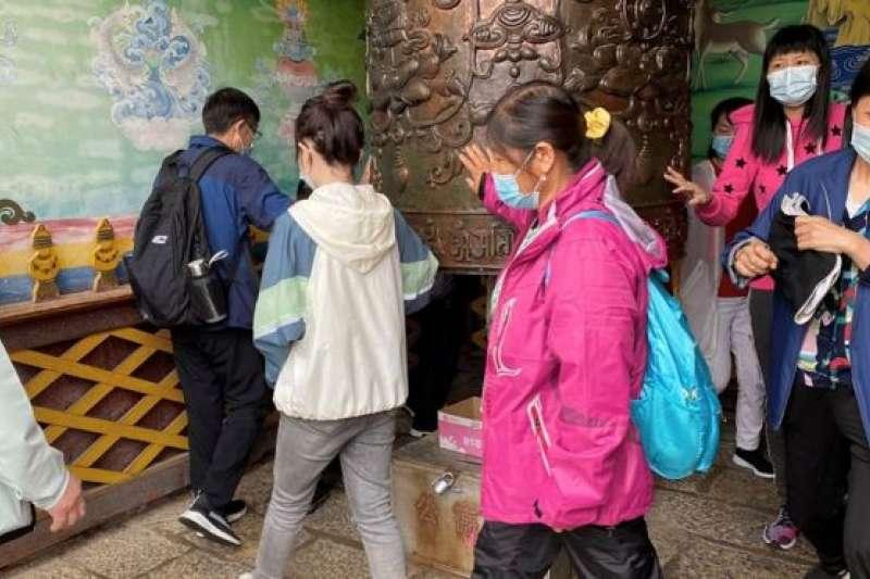 雲南一寺廟裡戴口罩的遊客在轉動禱告輪(BBC中文網)
