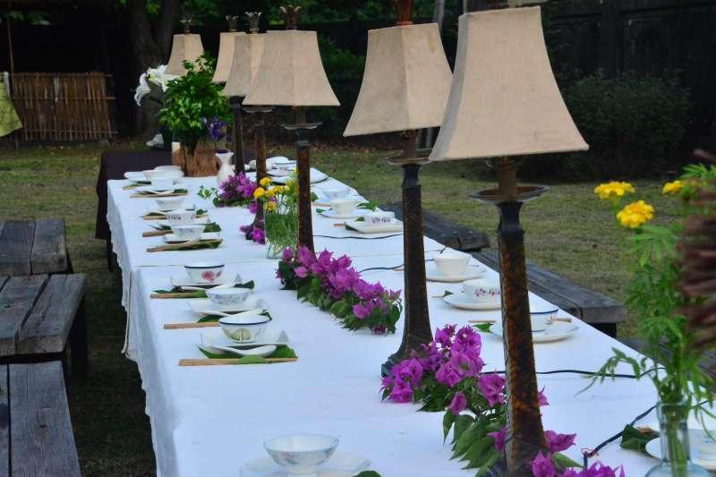 國本農場在草坪上鋪好白色桌布的長條餐桌,以九重葛和萬壽菊裝飾,並準備由農場現摘現煮的佳餚迎接賓客。(資料照,取自臉書臺東縣永續發展學會- 國本農場)