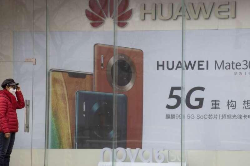 疫情期間一名婦女站在位於北京的華為手機5G廣告旁。(美國之音)