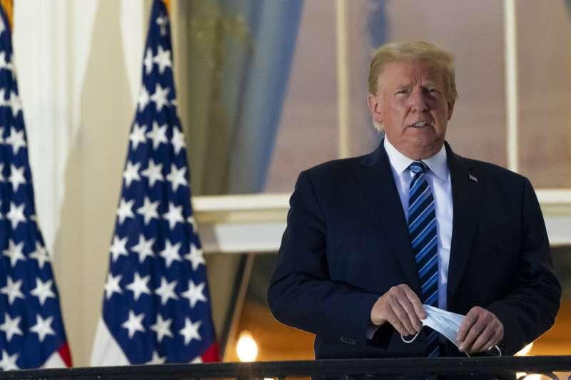 美國總統川普回到白宮後,立刻走上陽台、拿掉口罩,對媒體揮手致意。(美聯社)