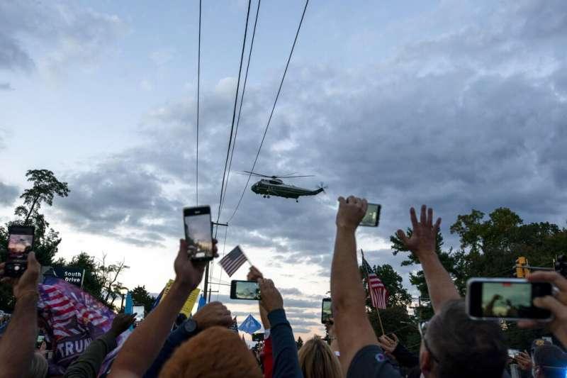 川普搭乘「陸戰隊一號」返回白宮,聚集在醫院外的支持者立刻拿出手機拍照。(美聯社)