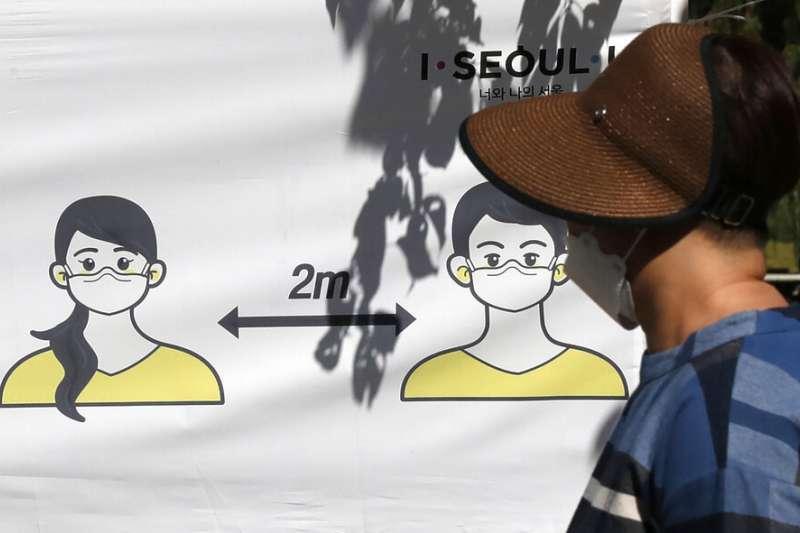 南韓疫情。首爾街頭的防疫海報,呼籲民眾保持至少2公尺的社交距離。(美聯社)