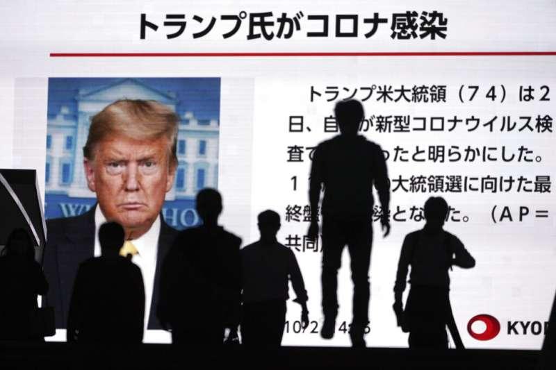 美國總統川普確診新冠肺炎的消息,出現在東京街頭的大型資訊看板上。(美聯社)