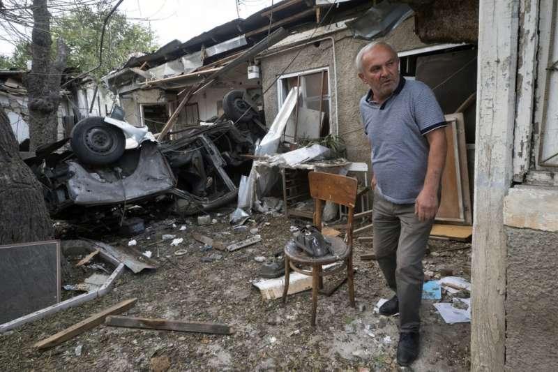 亞美尼亞與亞塞拜然在納卡地區爆發衝突,一名男子檢視被亞塞拜然攻擊後的房屋殘骸。(AP)