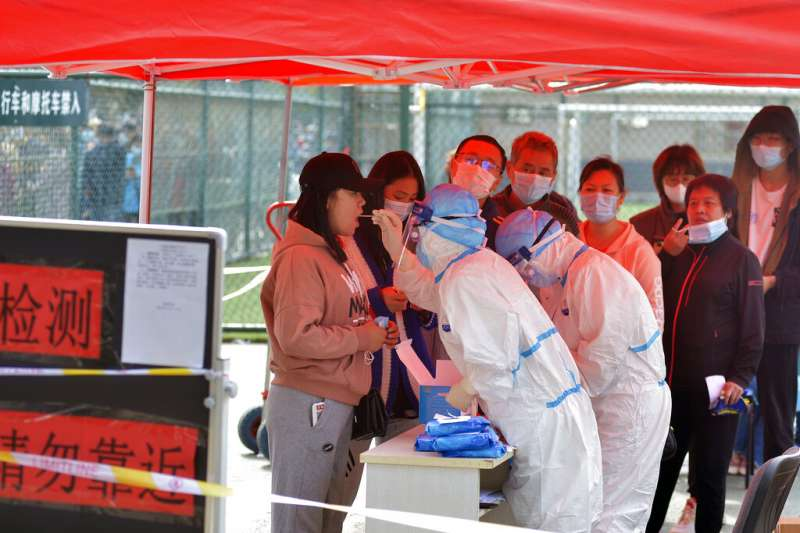 中國山東省青島市民排隊等候進行新冠病毒核酸檢測。(美聯社)