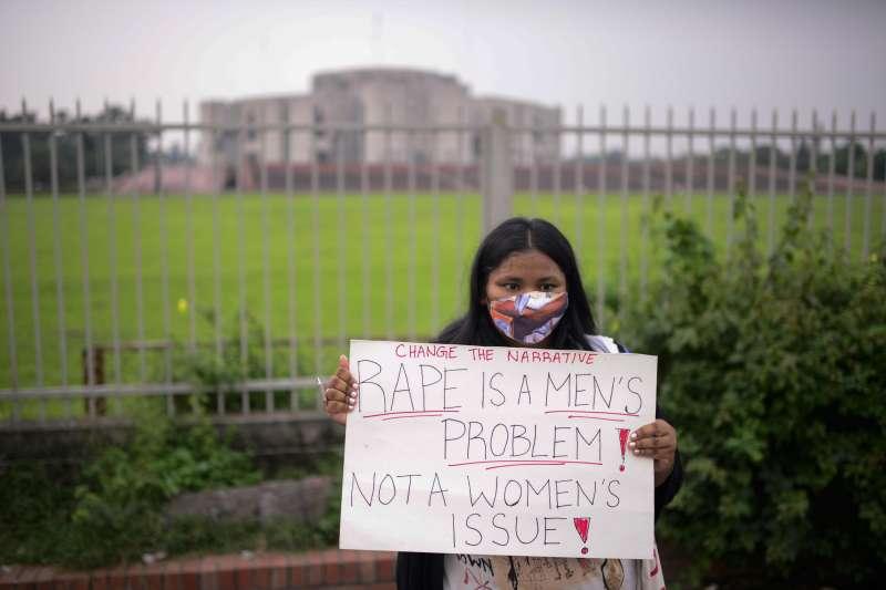 10月9日,孟加拉首都達卡國會外,一名婦女舉著標語抗議針對女性的暴力行為(美聯社)
