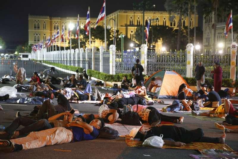 10月15日凌晨,泰國曼谷的示威學生在總理府外直接打地鋪休息。(AP)